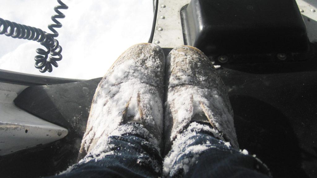 Schneebedeckte Schuhe im Helikopter